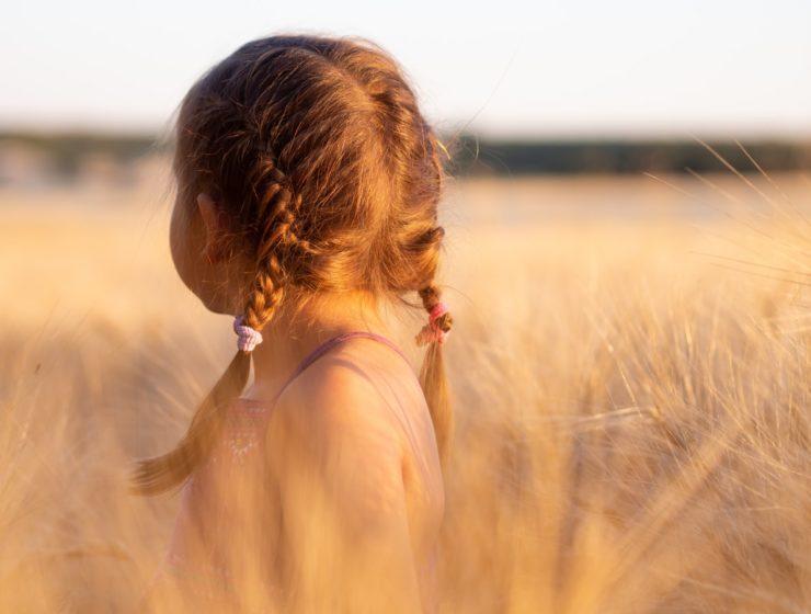 Fetiță care stă pe câmp și privește în depărtare