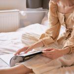 Femeie care stă în pat și citește o revistă