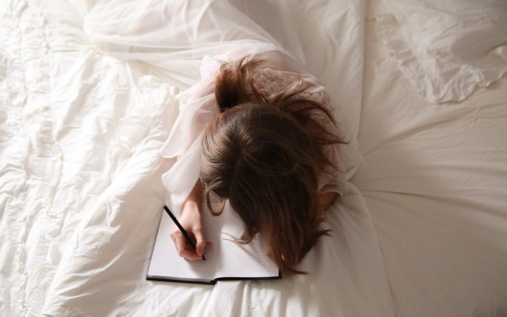 Femeie care stă în pat și scrie în jurnal