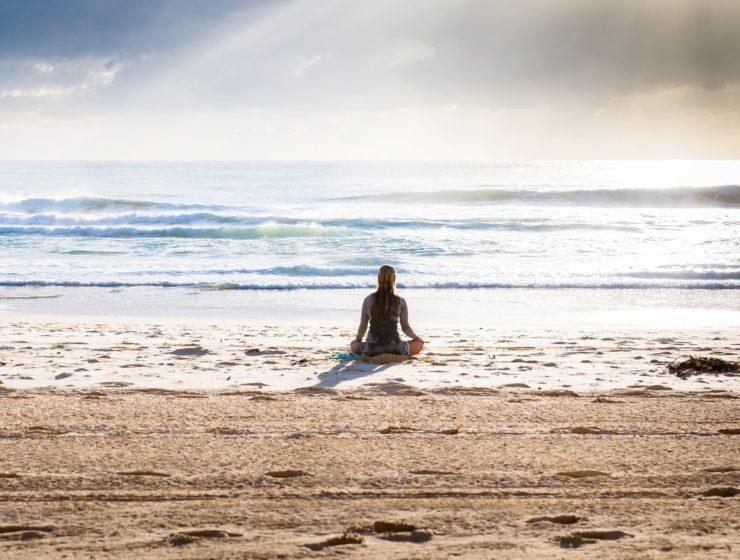 Femeie care stă pe plajă și meditează