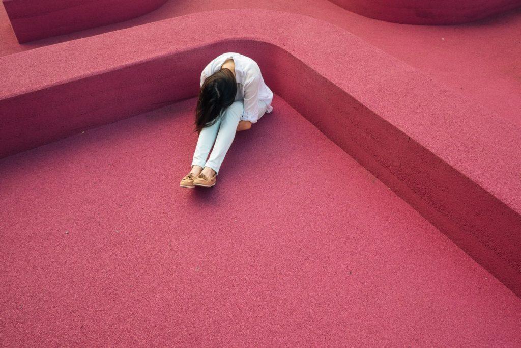 Femeie tristă care stă cu genunchii la piept