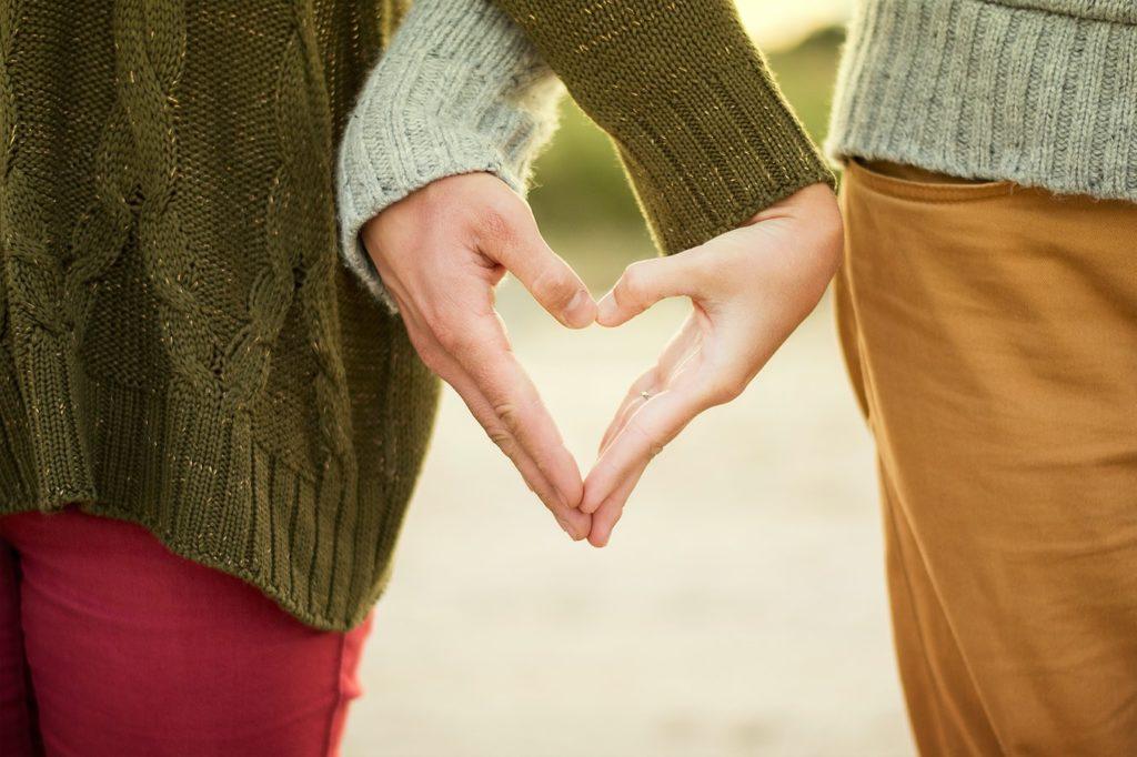 Mâinile unor îndrăgostiți care formează o inimă