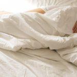 Persoană care doarme în pat și este învelită