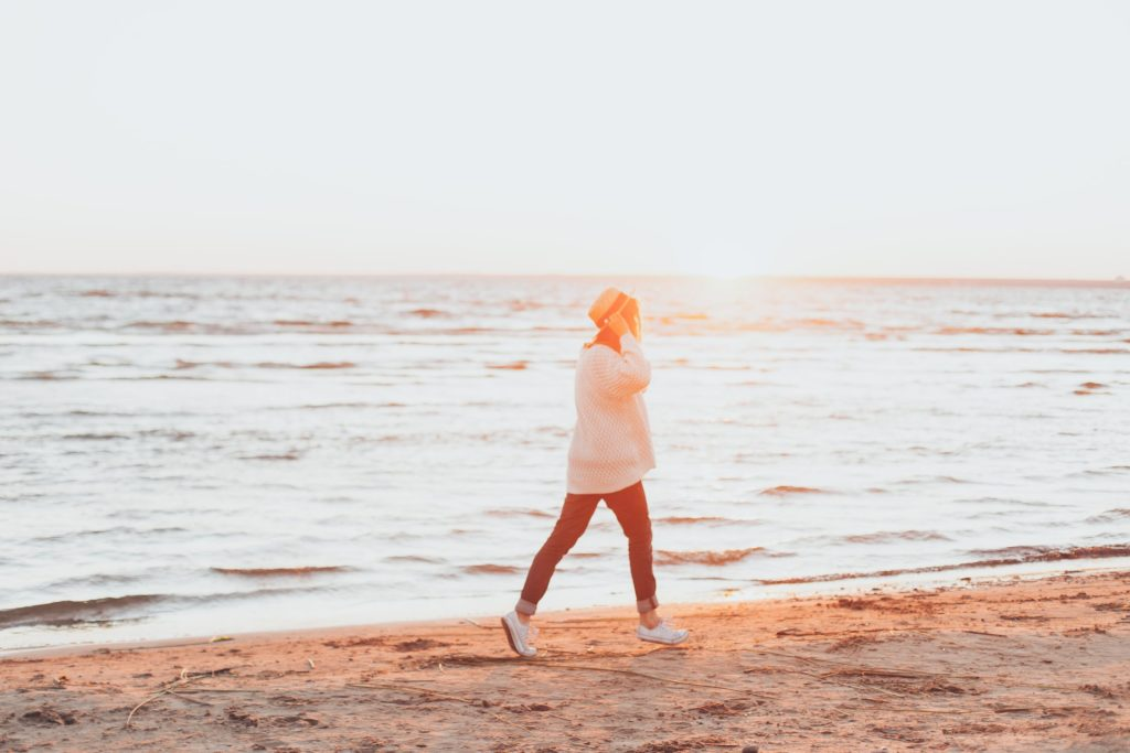 Tânără care se plimbă pe malul mării