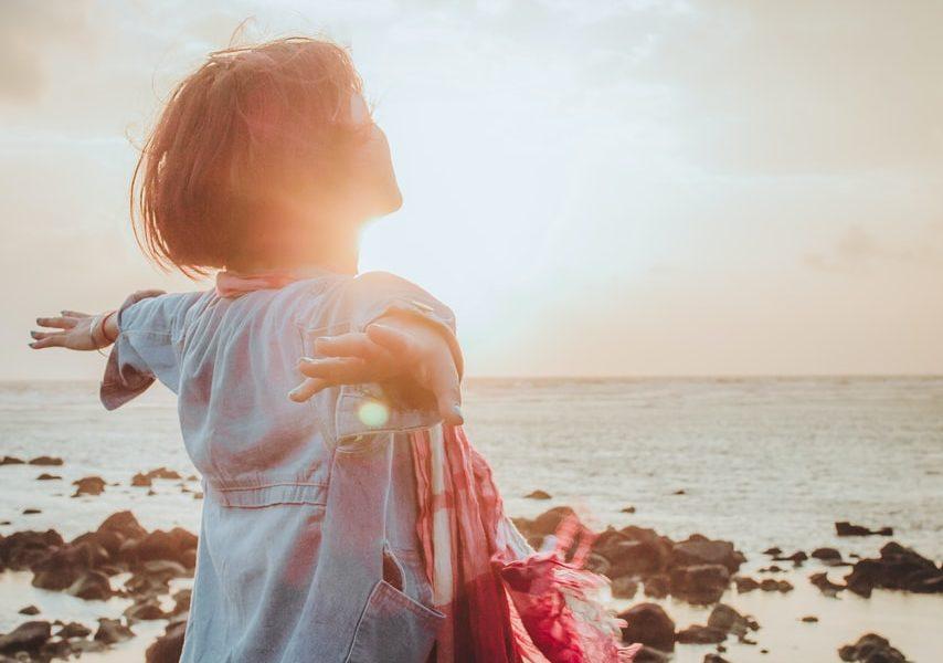 Tânără liniștită care stă la malul mării cu brațele întinse