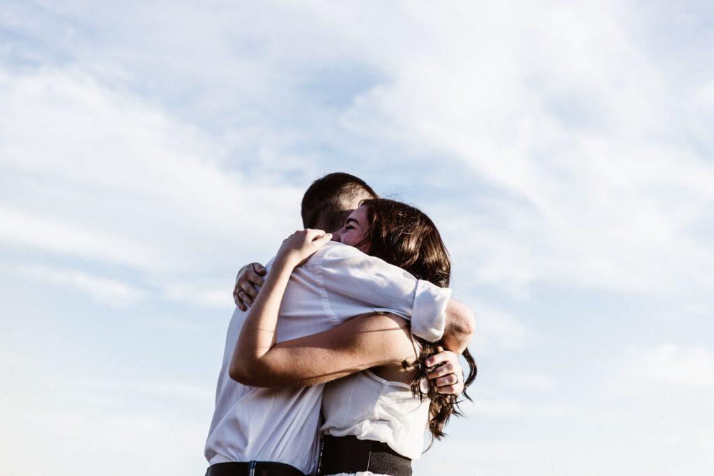 Doi oameni care se îmbrățișează