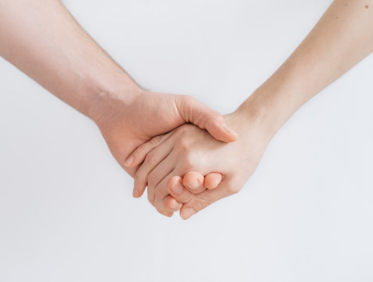 Două persoane care se țin de mână