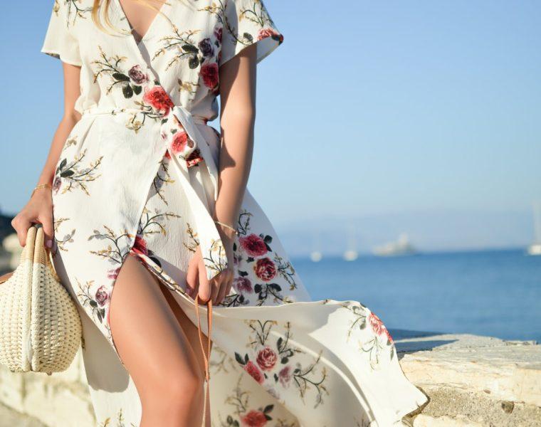 Femeie care poartă o rochie înflorată și se plimbă pe faleză