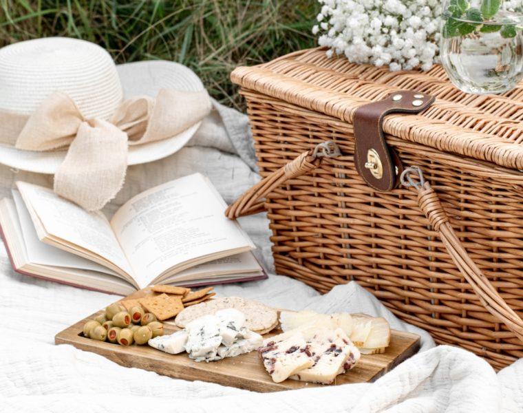 Coș de picnic, platou cu brânzeturi, carte și o pălărie
